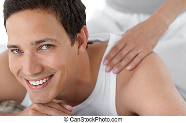 Portrait of a happy man receiving a massage from his girlfriend