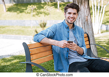 Portrait of a happy man sitting on the bench outdoors
