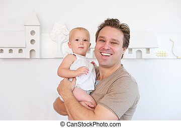 Portrait of a happy man smiling and holding cute baby
