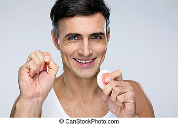Portrait of a happy man with dental floss over gray background