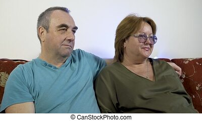 Portrait of a happy mature couple in their home watching tv together