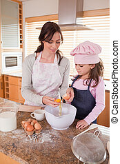 Portrait of a happy mother and her daughter baking