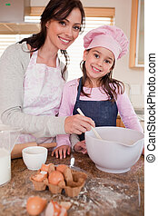 Portrait of a happy mother baking with her daughter