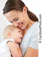 Portrait of a happy mother hugging cute baby
