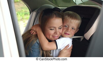 Portrait of a happy mother with her son in the car, the boy in the car seat.