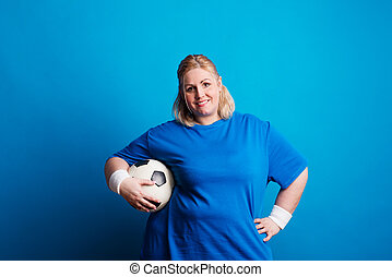 Portrait of a happy overweight woman with a ball in studio on a blue background.