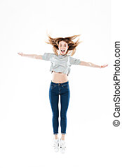Portrait of a happy pretty girl jumping with hands raised