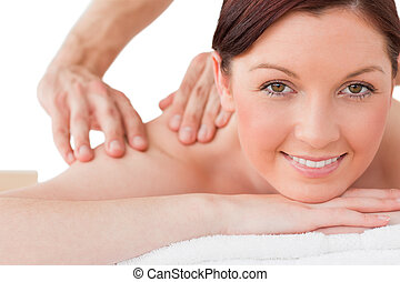 Portrait of a happy red-haired female posing while receiving a massage in a spa centre