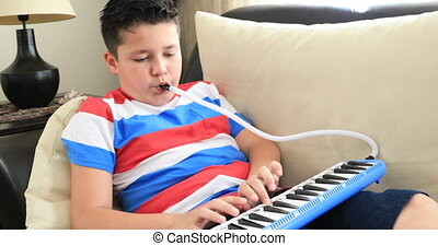 Portrait of a happy schoolboy playing melodica at home