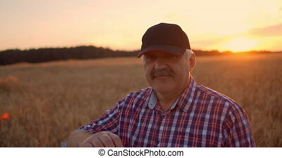 Portrait of a happy Senior adult farmer in a cap in a field ...
