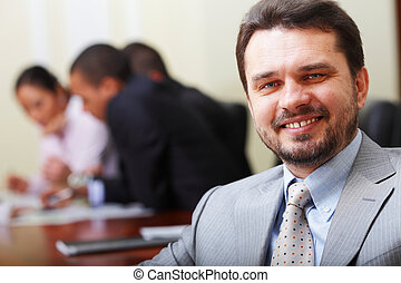 Portrait of a happy senior business man at office with his...