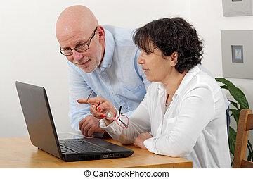 Portrait of a happy senior couple using laptop