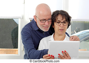 Portrait of a happy senior couple using tablet digital