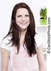 portrait of a happy smiling young woman in kitchen