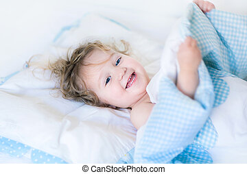 Portrait of a happy toddler waking up in the morning