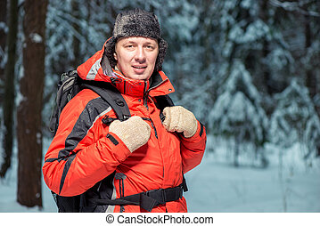 portrait of a happy tourist in a jacket hiking with a backpack in the winter forest