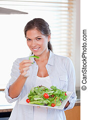 Portrait of a happy woman eating a salad
