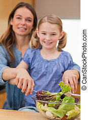 Portrait of a happy woman preparing a salad with her daughter