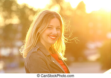 Portrait of a happy woman smiling at sunset