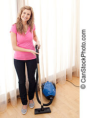 Portrait of a happy woman vacuuming