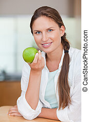 Portrait of a happy woman with an apple