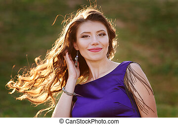 Portrait of a happy woman with curled hair outdoors at sunset sun