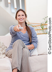 Portrait of a happy woman woman watching TV
