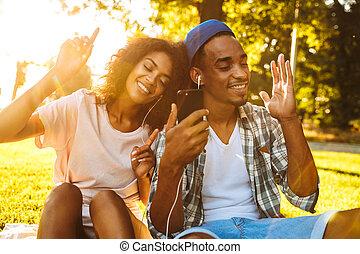 Portrait of a happy young african couple in earphones