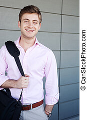 portrait of a happy young business man with laptop bag