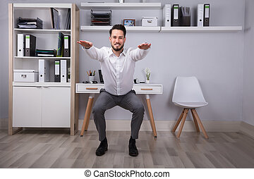 Businessman Doing Workout In Office