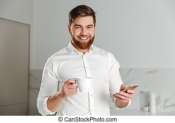 Portrait of a happy young businessman dressed in white shirt