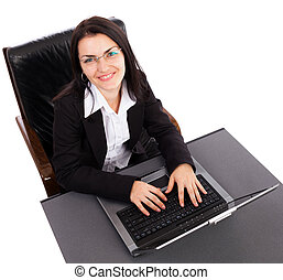 Portrait of a happy young businesswoman working on laptop while sitting in an armchair