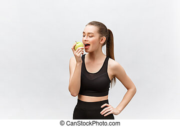 Portrait of a happy young caucasian woman holding and eating green apple over white background