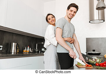 Portrait of a happy young couple cooking together