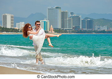 Portrait of a happy young couple having fun on the beach. Young man lifting his woman on beach. Couple enjoying a summer vacation.