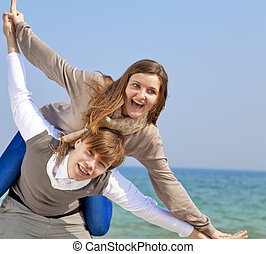 Portrait of a happy young couple having fun on the beach.
