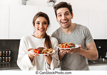 Portrait of a happy young couple holding dinner plates