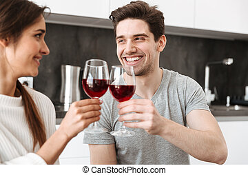 Portrait of a happy young couple holding glasses of wine