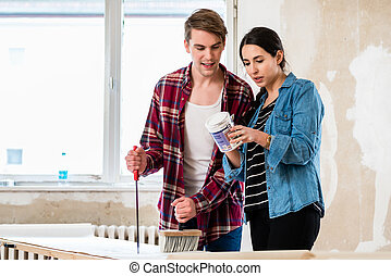 Portrait of a happy young couple holding tools for home remodeling