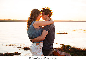 Portrait of a happy young couple kissing at the seaside