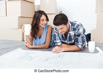 Portrait of a happy young couple looking at the blueprints