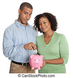 Portrait of a happy young couple with piggy bank