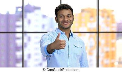 Portrait of a happy young dark-skinned hindu man shows thumb up. Handosme guy wearing blue formal shirt. Like gesture.