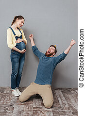 Portrait of a happy young family expecting child and celebrating