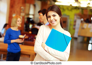 Portrait of a happy young female student in classroom