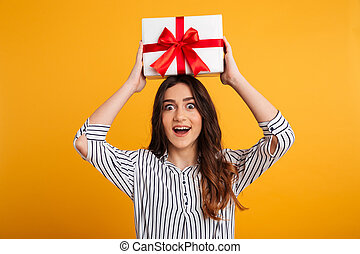 Portrait of a happy young girl holding gift box
