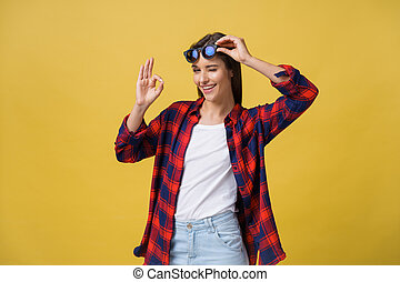 Portrait of a happy young girl in summer clothes showing ok gesture over yellow background.