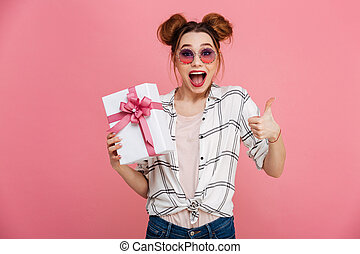 Portrait of a happy young girl in sunglasses holding gift box