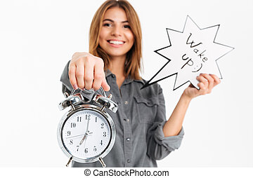 Portrait of a happy young girl showing alarm clock