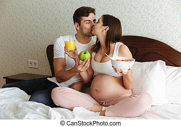Portrait of a happy young pregnant couple